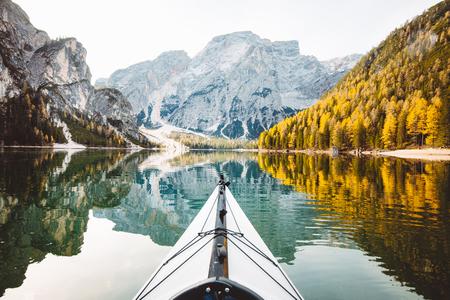 Hermosa vista de kayak en un lago tranquilo con increíbles reflejos de picos de montaña y árboles con follaje otoñal amarillo en otoño, Lago di Braies, Italia
