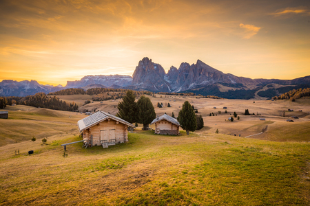Beautiful view of traditional wooden mountain chalets on scenic Alpe di Siusi