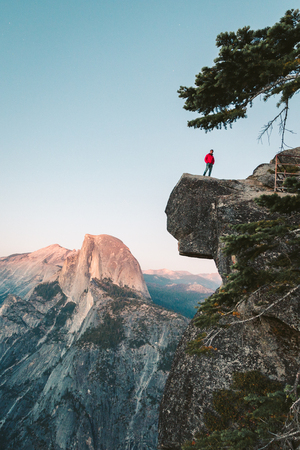 A fearless hiker is standing on an overhanging rock enjoying the view towards famous Half Dome at Glacier Point overlook