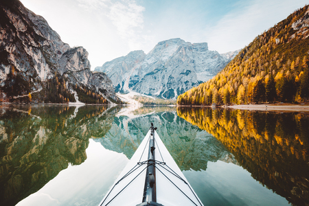Beautiful view of kayak on a calm lake with amazing reflections of mountain peaks and trees with yellow autumn foliage in fall, Lago di Braies, Italy 版權商用圖片