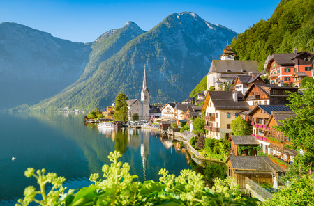 Classic postcard view of famous Hallstatt lakeside town in scenic golden morning light on a beautiful sunny day in summer