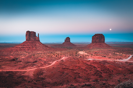 Classic panoramic view of scenic Monument Valley with the famous Mittens and Merrick Butte illuminated