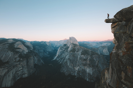 A fearless hiker is standing on an overhanging rock enjoying the view towards famous Half Dome at Glacier Point