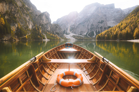 Beautiful view of traditional wooden rowing boat on scenic Lago di Braies in the Dolomites in scenic morning light