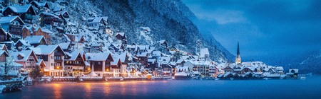 Panorama view of famous Hallstatt lakeside town in the Alps in mystic twilight during blue hour at dawn