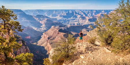 Panoramic view of young hiker overlooking famous Grand Canyon in beautiful golden evening light