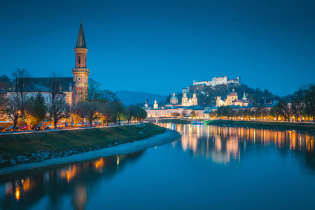 Classic twilight view of the historic city of Salzburg reflecting in beautiful Salzach river during blue hour at dusk