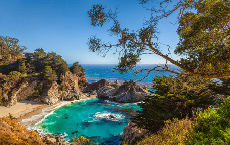 Classic postcard view of famous McWay Falls in scenic golden evening light at sunset on a beautiful sunny day