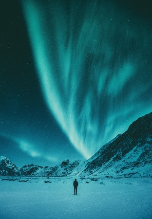 Young man standing on a remote beach watching the Northern Lights dance above mountains in winter, Lofoten Islands archipelago Фото со стока
