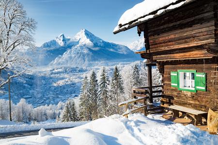 Splendida vista della tradizionale baita di montagna in legno nel pittoresco paesaggio montano del paese delle meraviglie invernale nelle Alpi