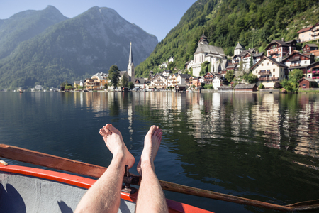 Beautiful view of young man relaxing on a traditional wooden rowing boat with Hallstatt lakeside town in the background on an idyllic sunny day in summer, Salzkammergut, Austria