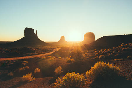 Classic view of scenic Monument Valley with the famous Mittens and Merrick Butte in beautiful golden morning light at sunrise in summer with retro vintage style filter effect, Arizona, USA