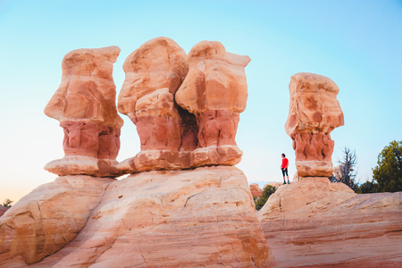 Beautiful view of male hiker standing between amazing Four Hoodoos sandstone formations in Devils Garden in beautiful evening light at sunset, Grand Staircase-Escalante National Monument, Utah, USA