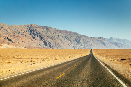 Classic panorama view of an endless straight road running through the barren scenery of the American Southwest in summer Фото со стока
