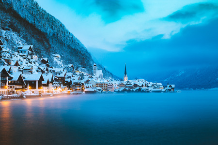 Panorama view of famous Hallstatt lakeside town in the Alps in mystic twilight during blue hour at dawn on a beautiful cold foggy day in winter, Salzkammergut region, Austria Stock Photo - 119003291