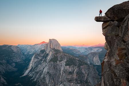 Un intrepido escursionista è in piedi su una roccia a strapiombo godendosi la vista verso la famosa Half Dome a Glacier Point si affacciano nel bellissimo crepuscolo serale, Yosemite National Park, California, USA Archivio Fotografico