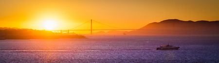 Panoramic view of famous Golden Gate Bridge illuminated in beautiful golden evening light at sunset in summer, San Francisco Bay Area, California, USA