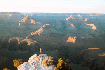 A male photographer is standing on a cliff taking in the amazing view over famous Grand Canyon National Park at sunset, American Southwest, USA