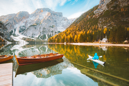 Beautiful view of famous Lago di Braies with traditonal rowing boat and young man in kayak at sunrise in fall, Dolomites, Italy 写真素材