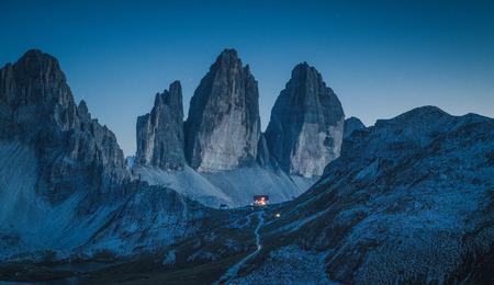 Splendida vista sulle famose montagne Tre Cime di Lavaredo nella catena montuosa delle Dolomiti con il famoso rifugio alpino Antonio Locatelli in una chiara notte stellata in estate, Alto Adige, Italia Archivio Fotografico