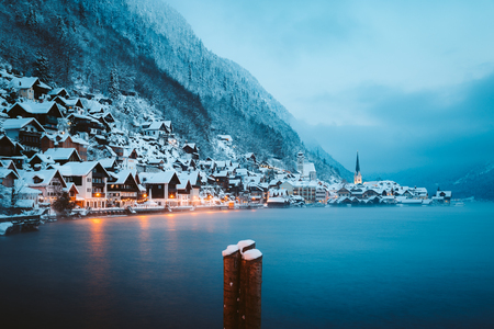 Panorama view of famous Hallstatt lakeside town in the Alps in mystic twilight during blue hour at dawn on a beautiful cold foggy day in winter, Salzkammergut region, Austria 免版税图像