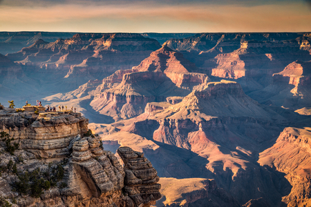 A group of hikers is standing on a steep cliff watching the sun set over famous Grand Canyon in summer, Grand Canyon National Park, Arizona, USA Stock Photo