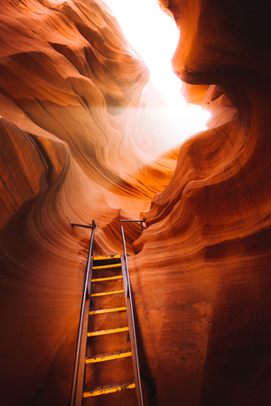 Beautiful view of amazing sandstone formations with a ladder leading toward a magic light beam in famous Antelope Canyon near the historic town of Page at Lake Powell, American Southwest, Arizona, USA Фото со стока