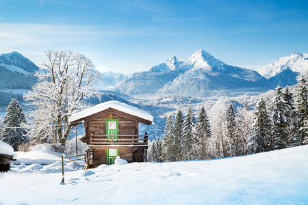Beautiful view of traditional wooden mountain cabin in scenic winter wonderland mountain scenery in the Alps