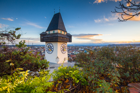 Classic panorama view of the historic city of Graz with famous Grazer Uhrturm clock tower in beautiful evening light at sunset, Styria, Austria Stock Photo
