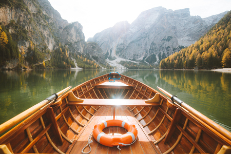 Beautiful view of traditional wooden rowing boat on scenic Lago di Braies in the Dolomites in scenic morning light at sunrise, South Tyrol, Italy