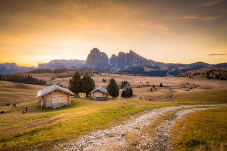 Beautiful view of traditional wooden mountain chalets on scenic Alpe di Siusi with famous Langkofel mountain peaks in the background in golden morning light at sunrise, Dolomites, South Tyrol, Italy Stock Photo