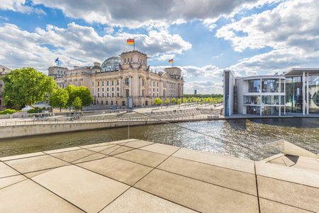 Panoramic view of Berlin government district with Spree river passing famous Reichstag building and Paul Lobe Haus on a beautiful sunny day with blue sky and clouds, central Berlin Mitte, Germany