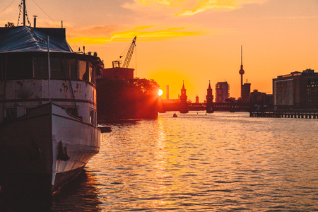 Panoramic view of Berlin skyline with famous TV tower and Oberbaum Bridge with old ship wreck lying in river Spree at dusk, Berlin Friedrichshain-Kreuzberg, Germany.