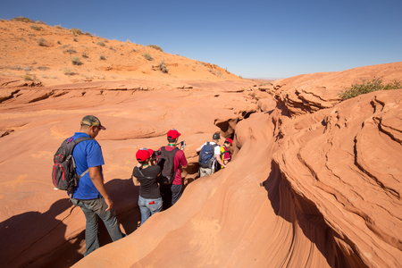 SEPTEMBER 17, 2016 - PAGE, ARIZONA: A group of tourists is entering famous Antelope Canyon near the historic town of Page at Lake Powell on a sunny day with blue sky, American Southwest, Arizona, USA Редакционное