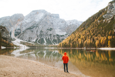Beautiful view of a young man standing on shore watching the sunrise at famous Lago di Braies in the Dolomites, South Tyrol, Italy