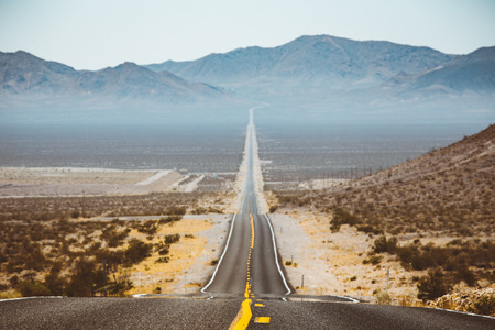 Classic panorama view of an endless straight road running through the barren scenery of the American Southwest with extreme heat haze on a beautiful sunny day with blue sky in summer 写真素材