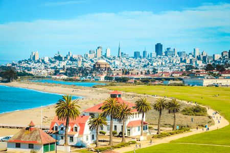 Panoramic view of San Francisco skyline with historic Crissy Field and former USCG Fort Point Life Boat Station (LBS) in the foreground on a beautiful sunny day with blue sky and clouds in summer, California, USA