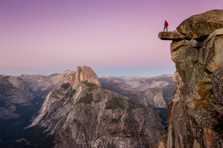 A fearless male hiker is standing on an overhanging rock at Glacier Point enjoying the breathtaking view towards famous Half Dome in beautiful post sunset twilight in summer, Yosemite National Park, California 版權商用圖片