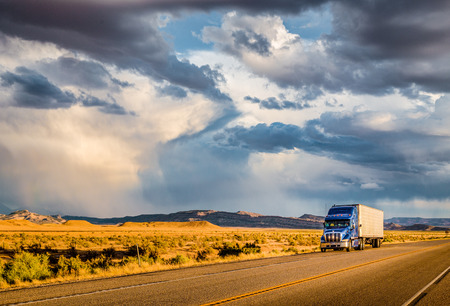Beautiful panorama view of classic semi trailer truck on empty highway with dramatic sky in golden evening light at sunset Stock Photo - 119086203