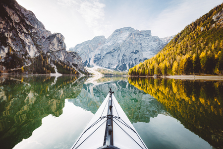 Beautiful view of kayak on a calm lake with amazing reflections of mountain peaks and trees with yellow autumn foliage in fall, Lago di Braies, Italy Stock Photo