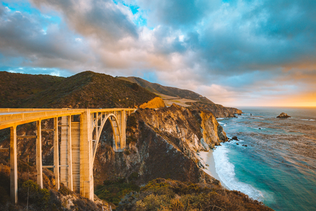 Scenic panoramic view of historic Bixby Creek Bridge along world famous Highway 1 in beautiful golden evening light at sunset with dramatic cloudscape in summer, Monterey County, California, USA Banque d'images - 119086254