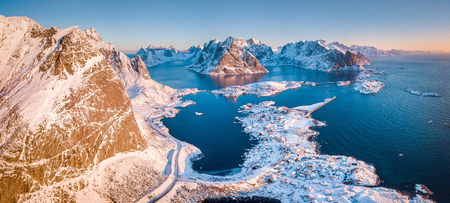 Aerial panoramic view of amazing Lofoten Islands winter scenery with famous Reine fishing village in beautiful golden morning light at sunrise, Norway, Scandinavia.