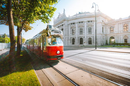 Famous Wiener Ringstrasse with historic Burgtheater (Imperial Court Theatre) and traditional red electric tram at sunrise with retro vintage style filter effect in Vienna, Austria 版權商用圖片