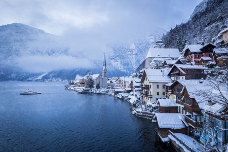 Classic postcard view of famous Hallstatt lakeside town with traditional passenger ship on Hallstattersee lake on a moody cloudy day with mystic fog in winter, Salzkammergut, Austria