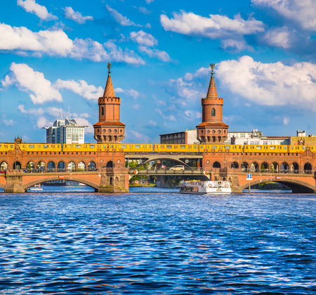 Beautiful view of famous Oberbaum Bridge at Spree river with excursion boat and Berliner U-Bahn on a sunny day with blue sky and clouds in summer, Berlin, Germany