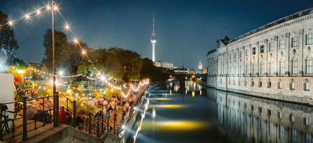 People dancing at summer Strandbar beach party near Spree river at Museum Island with famous TV tower in the background at night, Berlin, Germany