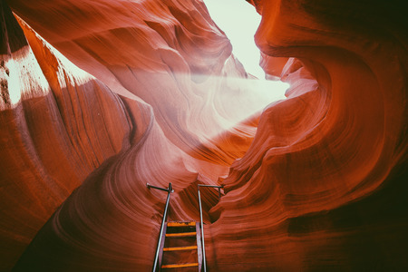 Beautiful view of amazing sandstone formations with a ladder leading toward a magic light beam in famous Antelope Canyon near the historic town of Page at Lake Powell, American Southwest, Arizona, USA Stock Photo