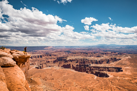 A male hiker is standing on the edge of a cliff enjoying a dramatic overlook of scenic landscape in beautiful Canyonlands National Park, Utah, USA 写真素材