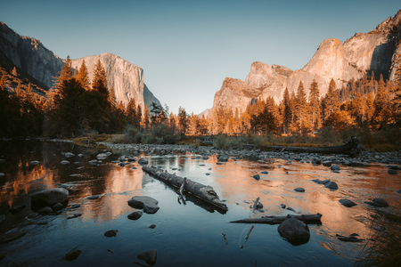 Classic view of scenic Yosemite Valley with famous El Capitan rock climbing summit and idyllic Merced river on a sunny day with blue sky and clouds in summer, Yosemite National Park, California, USA 版權商用圖片