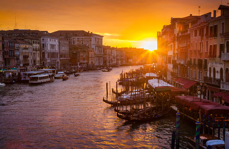 Classic panoramic view of famous Canal Grande from famous Rialto Bridge in beautiful golden evening light at sunset in summer, Venice, Italy